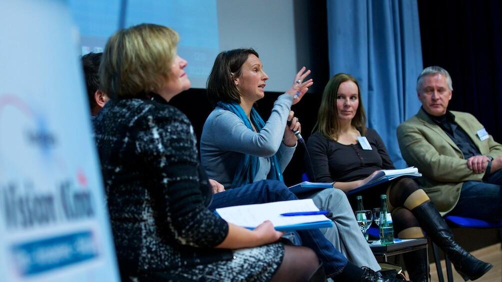 Diskutierende auf dem Podium