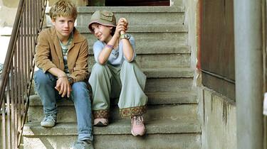Emil und Pony Hütchen sitzen auf einer Treppe.