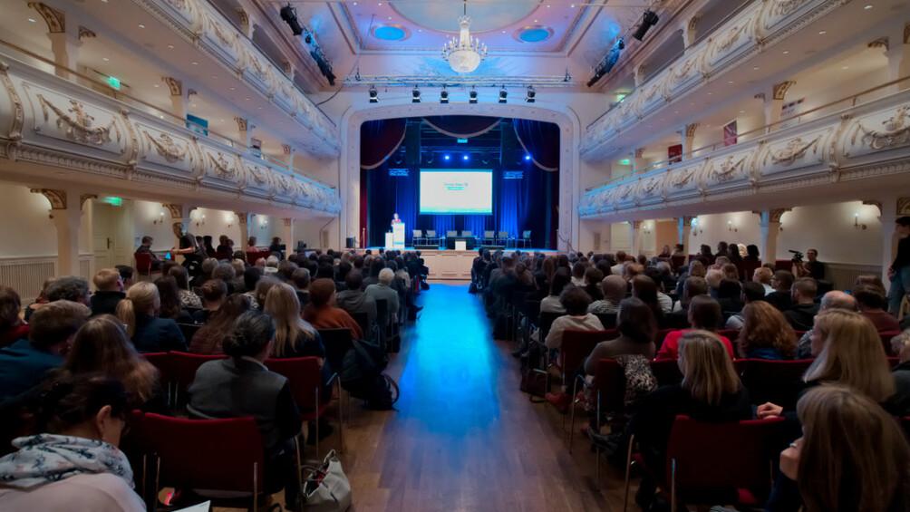 Kaisersaal, voll besetzte Stuhlreihen und Blick zwischen den Reihen auf die Bühne