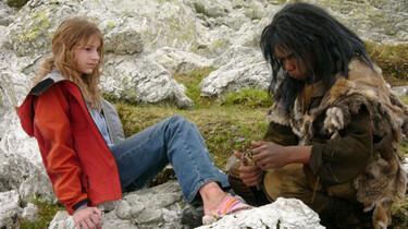Szenenbild: Sophie sitzt auf einem Stein während Baata einen Stein in der Hand hält