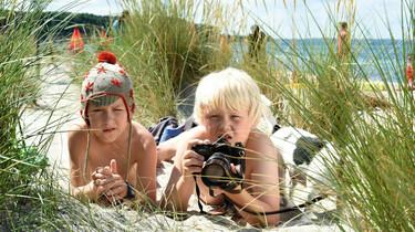 Szenenbild: Rico und Oskar liegen am Strand, in den Dünen versteckt und beobachten die Diebe