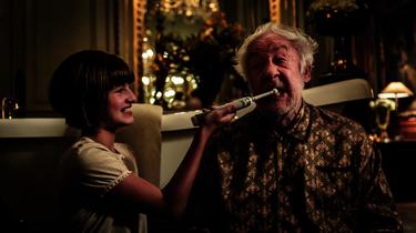 Tilda putzt ihrem Großvater die Zähne.