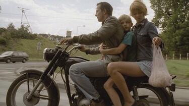 Szenenbild: Junge Frau, Mann und kleiner Junge sitzen auf einem Motorrad
