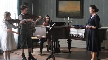"""Szenenbild: Kinder in einer 2guten Stube"""" beim Musikunterricht mit ihrer Lehrerin"""