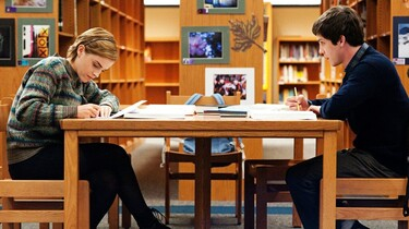 Szenenbild: Zwei Jugendliche sitzen sich an einem Tisch in einer Bibliothek gegenüber