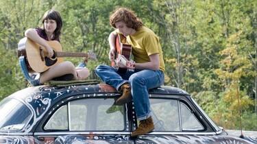 Szenenbild: Zwei junge Leute sitzen mit ihren Gitarren auf einem Autodach