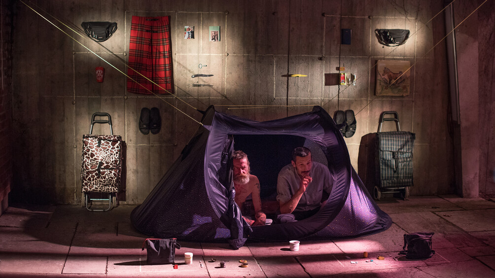 Zwei Männer sitzen in einem Zelt. Hinter ihnen sind Klamotten und kleine Gegenstände an die Wand gehängt.