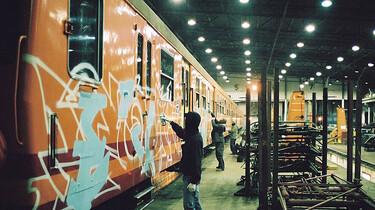Drei Grafitti-Sprayer besprühen mehrere organgefarbenen Wagons