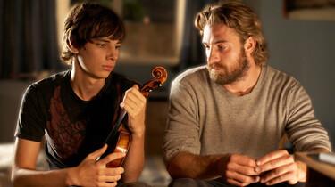 Szenenbild: Simon mit einer Geige. Neben ihm sitzt ein andere Mann