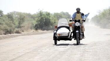 """Szenenbild: Ein Mann auf einem Motorrad mit einem """"Beigestell"""""""