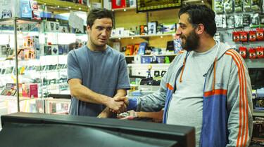 Szenenbild: Der Besitzer eines Ladens für gebrauchte Elektronik gibt sich vor einem Fernseher die Hand mit einem anderen Mann