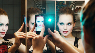 Szenenbild: Lena macht vor einem geteilten Spiegel ein Selfie mit dem Handy