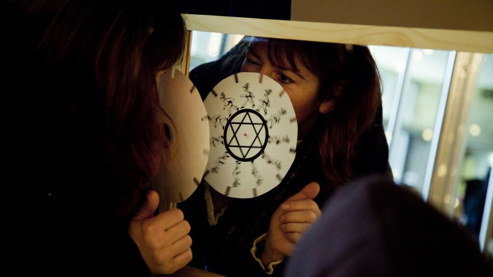 Eine Frau probiert eine Wunderscheibe vor dem Spiegel aus.