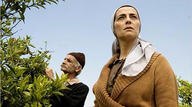 Szenenbild: Im Hintergrund steht ein alter Mann an einem Zitronenbraum. Im Vordergrund steht eine der Protagonistinnen und schaut in die Kamera
