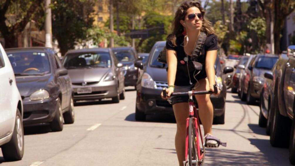Eine Frau mit Sonnenbrille fährt auf der Straße Fahrrad.