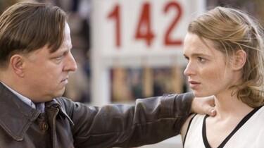 Szenenbild: Ein Mann hält eine junge Frau an der Schulter