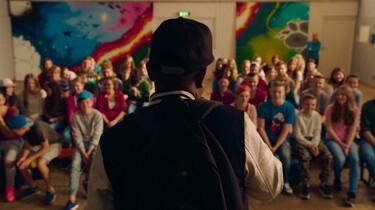 Szenenbild: Morris ist von hinten zu sehen, er steht vor einer großen Gruppe von Jugendlichen, offenbar in einer Schule