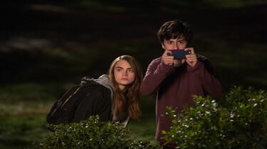 Szenenbild: Margo und Quentin beobachten etwas, halb hinter einer Hecke verborgen in der Nacht