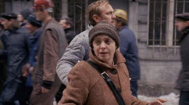 Szenenbild: Die Heldin in Bewegung, im Hintergrund Arbeiter
