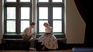 Szenenbild: Marcus und Olivia sitzen einander zugewandt auf einer Fensterbank