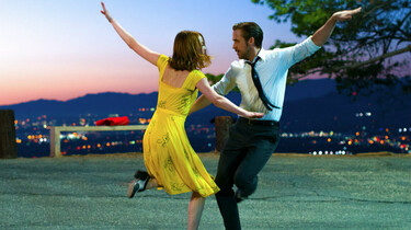 Szenenbild: Die beiden Protagonisten, Mia und Sebastian, tanzen mit ausgebreiteten Armen