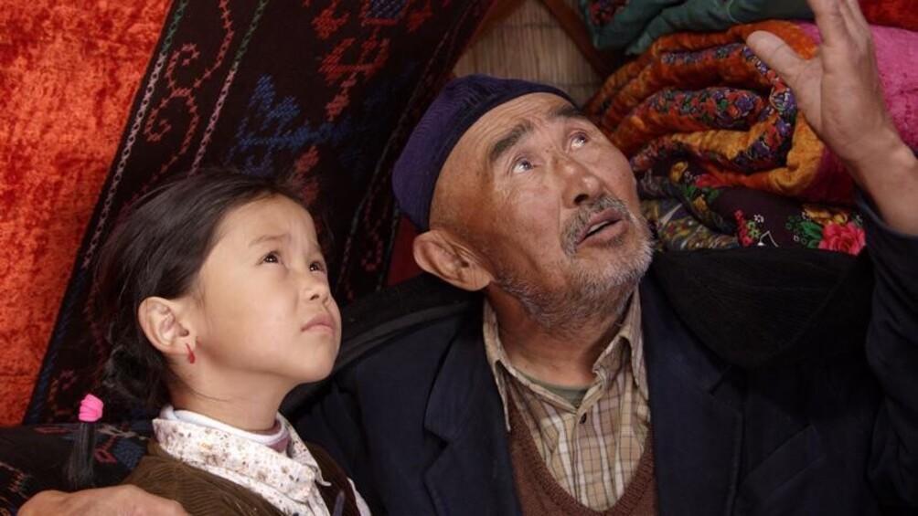 Kleines Mädchen und alter Mann schauen gemeinsam in den Himmel