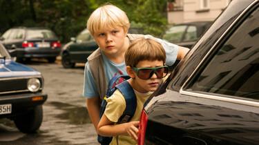 Szenenbild: Rico und Oskar verstecken sich hinter einem Auto, um Beobachtungen anzustellen