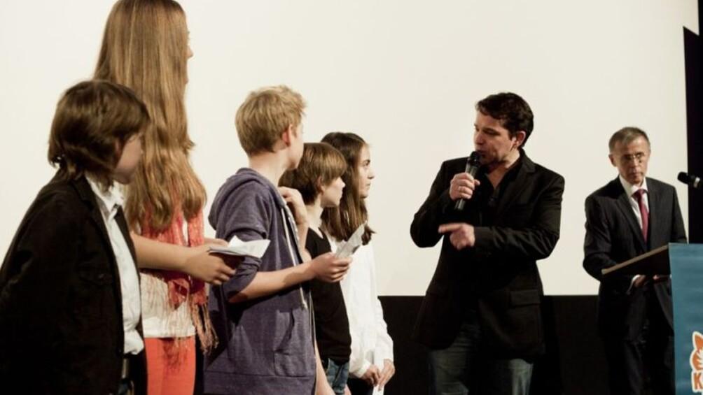 Die Kinderjury wird von Moderator Juri Tetzlaff befragt, im Hintergrund FFA Vertreter Frank Völkert