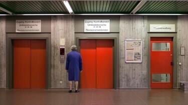Szenenbild: Ein Mann steht vor drei roten Fahrstühlen