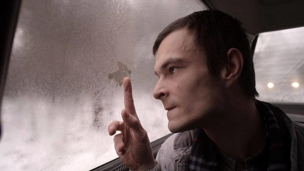 Ein junger Mann sitzt im Auto und schaut aus dem Fenster. Mit seinem Finger wischt er an der beschlagenen Scheibe.