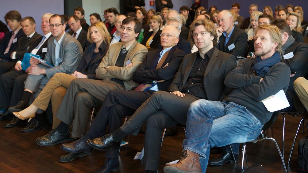 Kongressteilnehmer auf Stühlen sitzend, darunter Sönke Wortmann