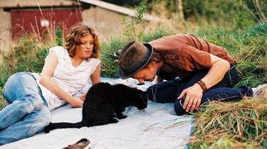 Szenenbild: Ein Mann und eine Frau sitzen auf einer Decke um eine schwarze Katze herum