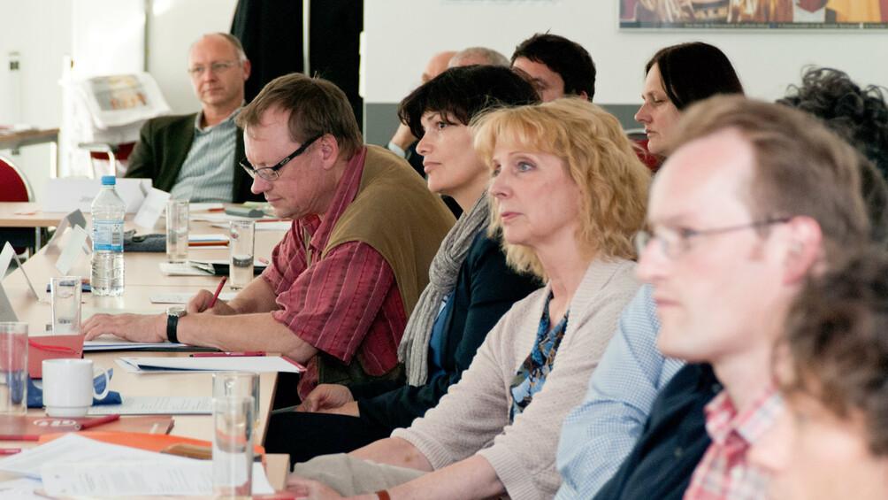 Lehrkräfte bei einer Fortbildung seitlich an Tischen sitzend