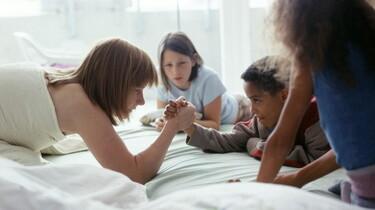 Szenenbild: Kinder auf einem Bett machen Armdrücken