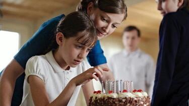 Szenenbild: Zwei Mädchen halten einen Kuchen in der Hand