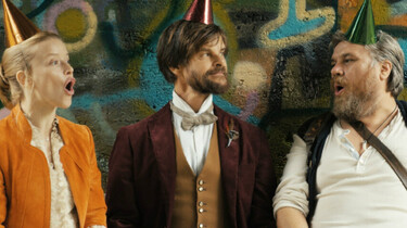 Szenenbild: Eintagsfliege, Fuchs und Wildschwein vor Wand mit Graffitti mit lustigen Hüten auf dem Kopf singend