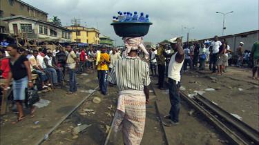 Eine Frau transportiert Plastikflaschen auf dem Kopf.