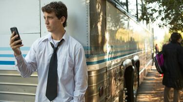 Jazzdrummer Andrew lehnt in weißem Hemd und Krawatte an einem Bus, schaut auf sein Handy