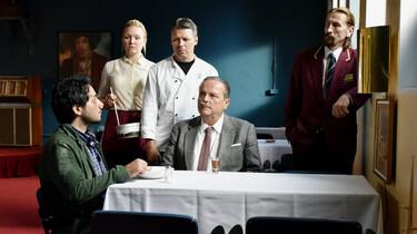 Szenenbild: Szene im Restaurant: Wikström und Khaled an einem Tisch sitzend, dahinter steht das restliche Personal