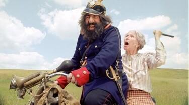 Der Räuber Hotzenplotz und die Oma auf dem Fahrrad. Die Oma will Hotzenplotz schlagen.