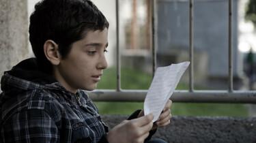 Szenenbild: Der 12-jährige Veysel liest einen Zettel