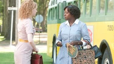 Szenenbild: Eine schwarze Hausangestellt in Uniform spicht mit Skeeter, im Hintergrund ein gelber Bus