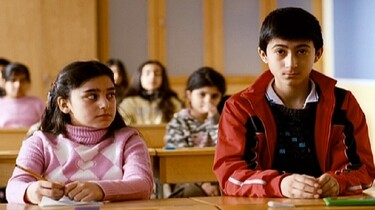 Szenenbild: Zwei Kinder im Klassenzimmer am Tisch sitzend