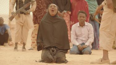 Szenenbild: Frau in schwarzem Tschador kniet auf dem sandigen Boden und schreit
